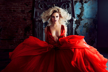Fashion photo of young magnificent woman. Running towards camera. Seductive blonde in red dress with fluffy skirt