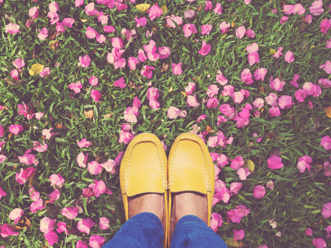 Selfie feet wearing yellow shoes on pink bougainvillea flower an