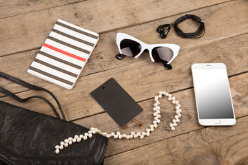 women set with bag, smart phone, sunglasses, notepad, headphones, tag and pearl on brown wooden desk
