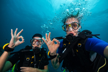 Scuba divers showing OK sign underwater