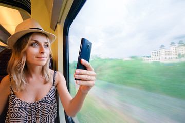 Enjoying travel. Young pretty woman traveling by the train sitting near the window using smartphone, taking photo.
