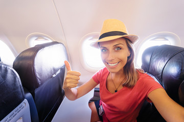 Travel and technology. Young woman in plane taking selfie while sitting in airplane seat.