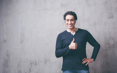 Great job! Happy young Arabic man in casual wear showing his thumb up while standing against grey background