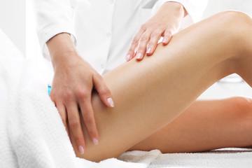 Ujędrniający masaż uda. Masażystka masuje udo
