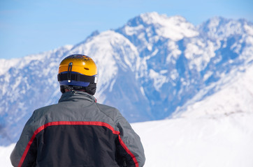 Man in black coat and yellow helmet watch on mountain peaks on ski resort. Winter extreme sport concept. Copy space for advertising.