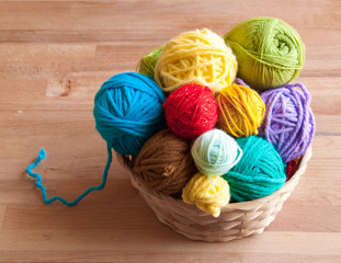 Many colorful wool balls in a basket