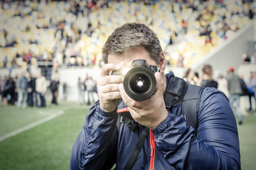 Photographer takes a photo at the stadium.