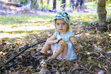 Cute little girl is sitting on the ground , playing in mud