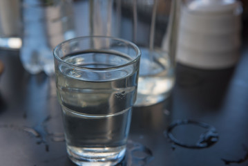 Cold water in a glass on a wooden black table.