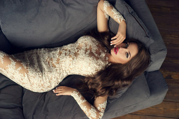 Young sexy woman in white lace evening dress lyuing on gray couch. Top view. Gorgeous glamorous girl with long brunette curly hair, makeup and red lips looking at you