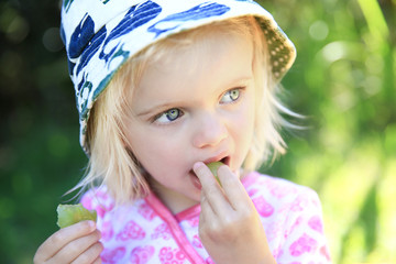 Adorable little girl eating green grapes