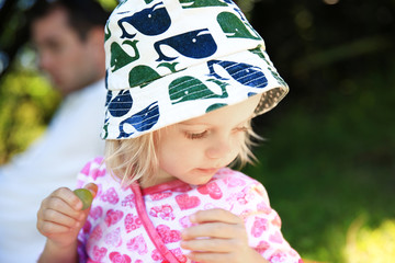Adorable little girl in holding green grape in hand