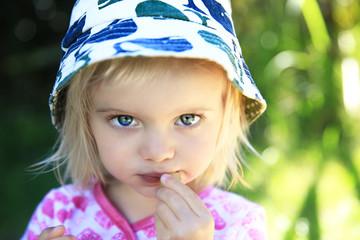 Adorable little girl eating green grapes