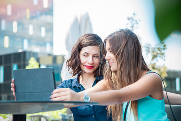 two beautiful young women taking a selfie with a tablet, in a business compound