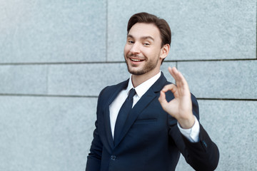 Everything is OK! Successful young businessman in formalwear gesturing OK sign and smiling while standing in front of the grey wall