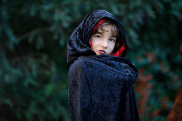 Boy of younger school age in a black-red cloak portrays the evil sorcerer.
