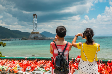 couple taking photo of Nanshan sculpture