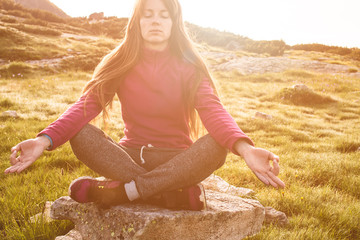 Woman sits in lotus position at sunrise