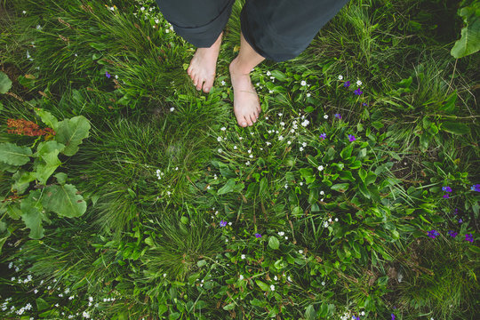 Female standing barefoot on green grass and flowers