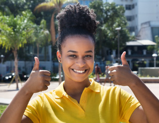 Beautiful woman with amazing hairstyle showing both thumbs up