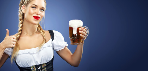 Advertisement with copy space. Banner format. Young sexy Oktoberfest waitress, wearing a traditional Bavarian dress, serving big beer mugs on blue background.