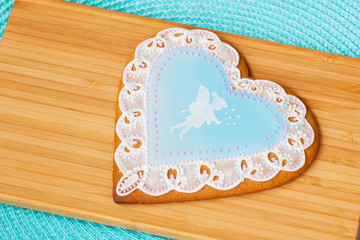 Beautiful pastel blue gingerbread with an openwork pattern and the image of a cute little fairy, background  wooden boards