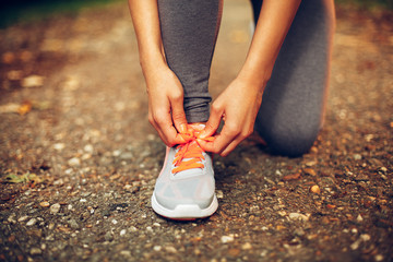 Close-up of female runner lacing her shoes
