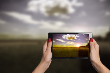 hands holding a tablet taking beautiful photographs of nature in sunset improving vision