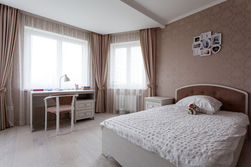 Interior of a bedroomwith a large bed in light brown tones for little girl