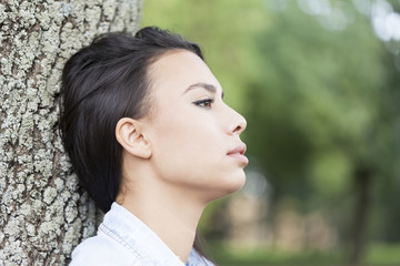 A young woman leaning on a tree