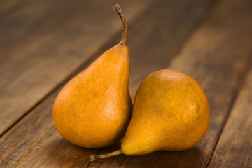 Two ripe Bosc pears on dark wood (Selective Focus, Focus on the front of the pears)