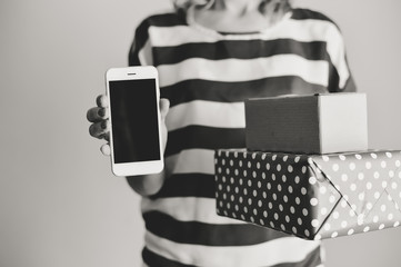Female holding using a smartphone and shopping box. Black and white closeup view