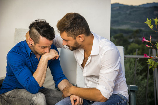 Portrait of two handsome men having trouble in relationship while sitting hugging and sad on balcony chairs.