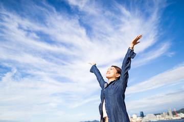 空に向かって手を広げる女性