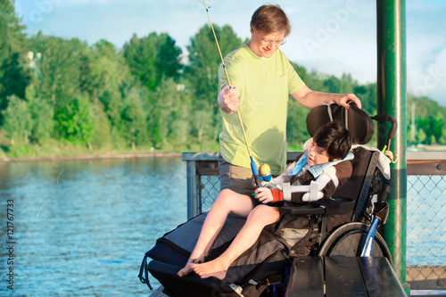 Father fishing off pier with disabled son in wheelchair for Fishing license for disabled person