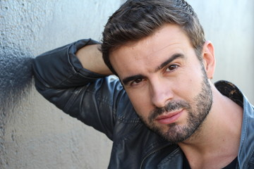 Male with a beard and mustache, dressing in a leather jacket and v-neck tee, is leaning against the wall, thinking outside