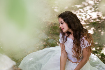 Beautiful girl with curly hair wear long white dress like a bride, sitting on a road. Photo taken from adove