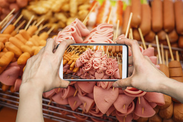 A tourist using smartphone camera taking a photo of ham and sausage sticks