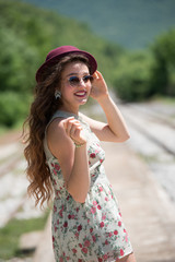Portrait of a pretty girl with curly hair wear floral dress, sunglasses and red bowler hat, walking on a old docks train station