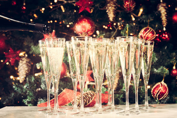 Wall Mural - Filling up glasses for party. Glasses of champagne with Christma