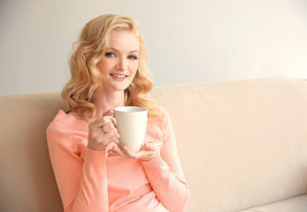 Beautiful girl drinking coffee on couch