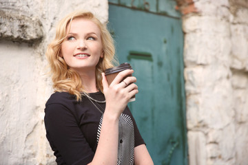 Beautiful girl with cup of coffee on street