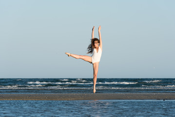Woman with long curly hair and excellent body wear white monokini, make a dance moves at the beach. Sea and sky as background