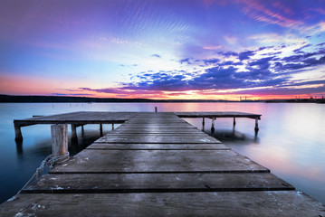 Wooden pier on a blue lake sunset and smooth reflection on water