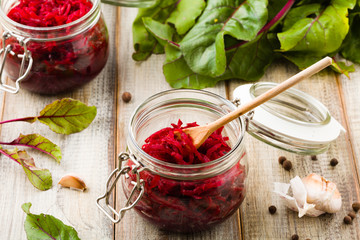 Grated beetroot marinated in jars. Wooden background.