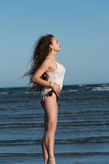 Woman with long curly hair wear bottom bikini and white shirt, standing in sea water. Sea and sky as background