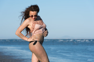 Woman with long curly hair wear bottom bikini, sunglasses and wear spaghetti strap, on the beach. Sea and sky as background