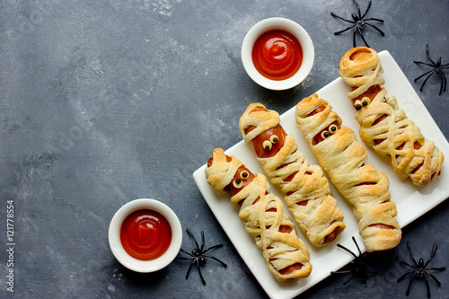 Halloween background. Funny sausage mummies with ketchup for halloween