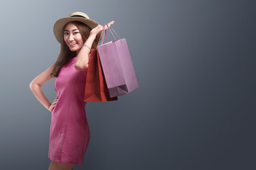 Happy asian woman with hat holding up shopping bags