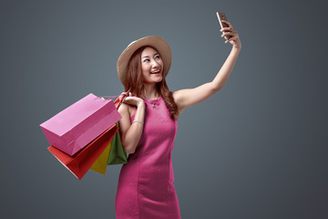 Portraits of cheerful asian woman in hat and bright clothes with shopping bags taking selfie